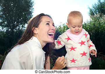 Portrait of a young mother smiling with cute baby outdoors