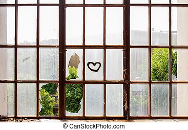 Heart painted on broken windows of abandoned building