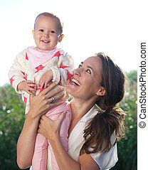 Portrait of a happy mother holding cute baby outdoors