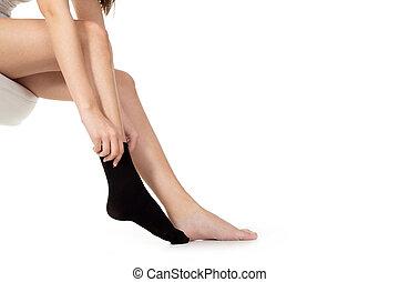 woman pulling socks on