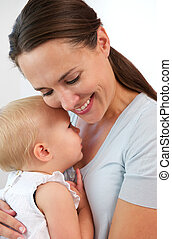 Portrait of a smiling mother hugging cute baby girl