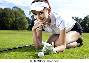 Pretty girl playing golf on grass in summer
