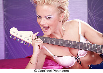 sexy woman with guitar in bed
