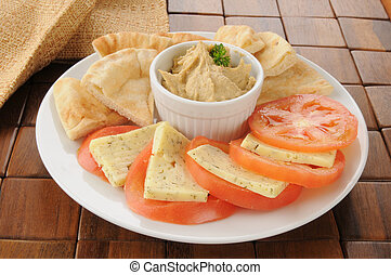 Garlic spice hummus with pita bread wedges, tomato and dill...
