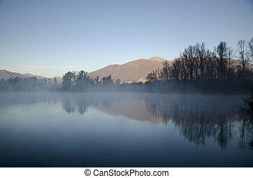 Foggy lake and mountain - Mountain and trees reflected in a...