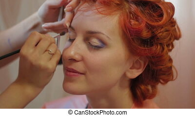 Putting on eyeshade - Makeup artist putting on eyeshade....