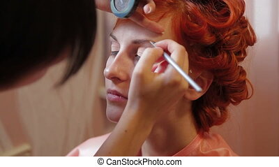 Putting on make-up on eyebrows. Close-up
