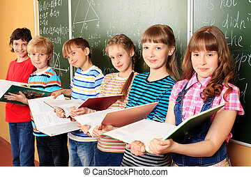 education - Group of happy schoolchildren standing with...