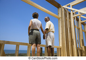 Couple at new home site - African American middle aged...