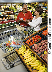 Couple grocery shopping. - Smiling middle aged African...