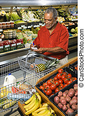 Man grocery shopping - Middle aged African American man in...
