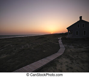 Beach house. - Sunset over coastal beach house with wooden...