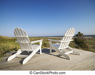 Deck chairs at beach. - Two adirondack chairs on wooden deck...