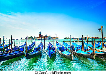 Venice, gondolas or gondole and church on background. Italy...