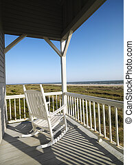 Porch at beach. - Rocking chair on porch with railing...