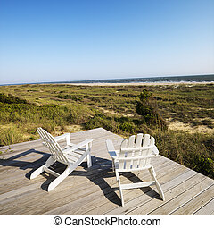 Deck chairs on beach. - Two adirondack chairs on wooden deck...