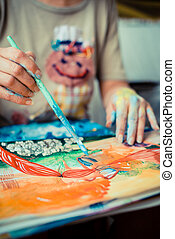 particular of woman painter hand painting in her studio
