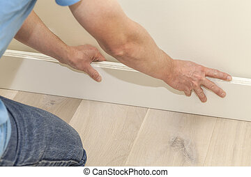 Fitting the skirting board - Mans hands fitting new wooden...