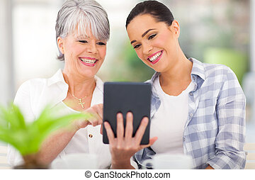 senior mother using tablet computer with daughter - happy...