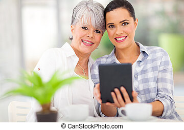 daughter using tablet pc with her middle aged mother