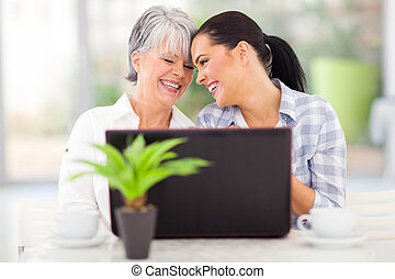 happy middle aged woman and adult daughter using laptop at...