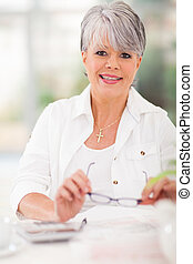 middle aged woman doing home finances - portrait of middle...