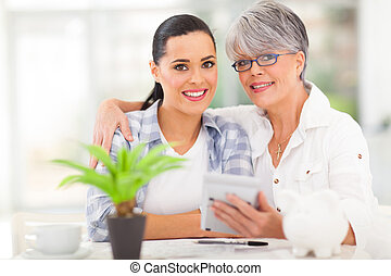 senior mother helping daughter calculate her finances -...