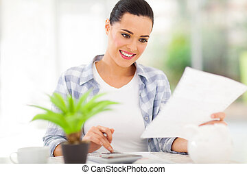 young woman paying bills - young woman paying her bills at...