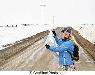 Woman holding map. - Young woman in winter clothes standing...