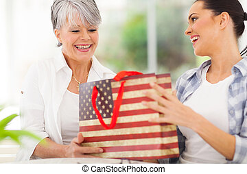 young woman giving her senior mother a gift
