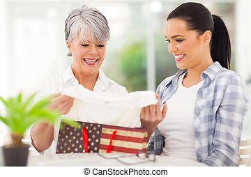 senior woman looking at her birthday gift - happy senior...
