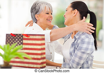 senior woman receiving a gift from adult daughter - cheerful...