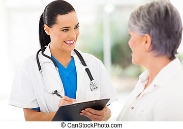 pretty young nurse talking to senior patient - beautiful...