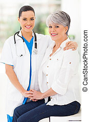 caring nurse comforting middle aged patient in office