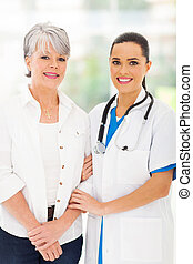 caring nurse standing with senior patient in office
