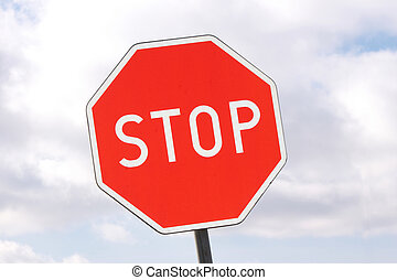 Road sign - stop - on cloudy sky background