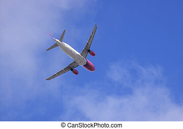 Jet airplane on almost clear blue sky witch some clouds