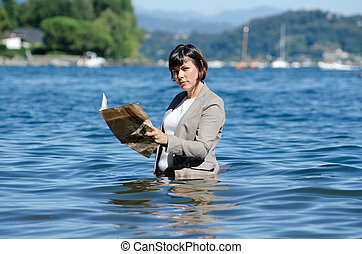 Business woman reading financial newspaper in the water -...