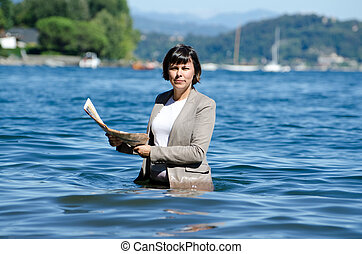 Woman standing in the water with a newspaper - Elegant woman...