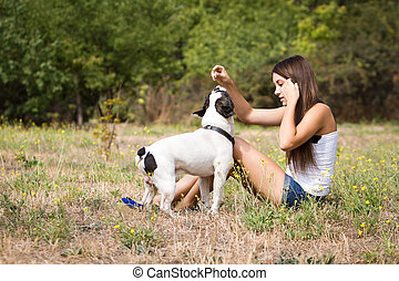 Teenager girl feeding her doggy - Teenage brunette girl...