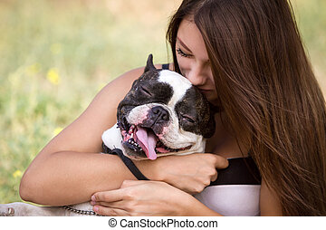 Young girl kissing her dog - Teenage brunette girl playing...