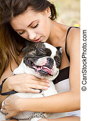 Attractive young girl holding her bulldog - Teenage brunette...