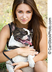 Pretty young lady holding her bulldog - Teenage brunette...