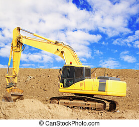 Yellow earthmover with cloudy sky