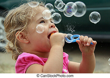 Blowing Bubbles - little child blowing bubbles taken in...