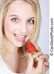 blonde woman eating strawberry
