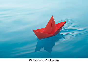 paper boat sailing - red paper boat sailing on water causing...