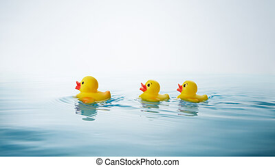 mother and children - two yellow rubber ducklings following...