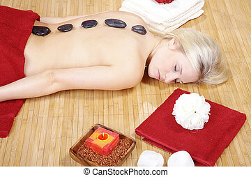 woman at spa with hot stones