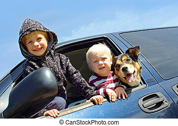 Children and Dog Leaning Out Minivan Window - Two happy...